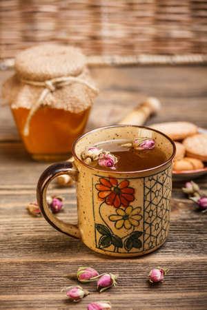 Schwarzer Tee im rustikalen Becher mit Blume Symbol photo