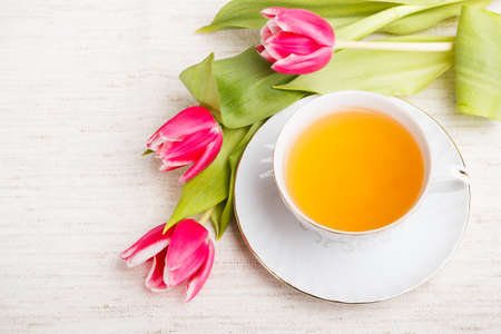 Tea cup with red tulips photo