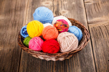 basket embroidery: Knitting yarn in basket on rustic wooden background