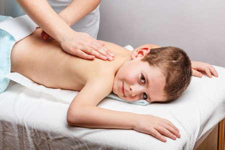 Lachende jongen liggend op de massagetafel