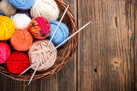 wool fiber: Bolas de lana en una cesta con agujas de tejer