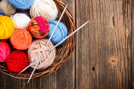 gomitoli di lana: Palle di filato in un cesto con i fn Archivio Fotografico