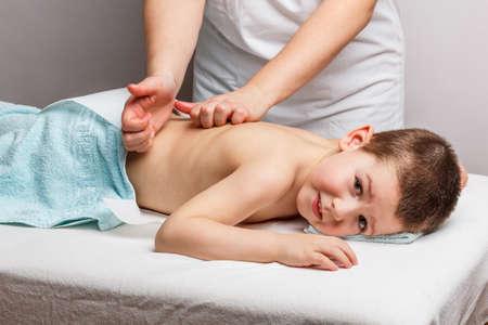 Little boy liegend auf einer Massageliege