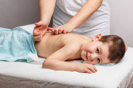 Little boy lying down on a massage bed Stock Photo