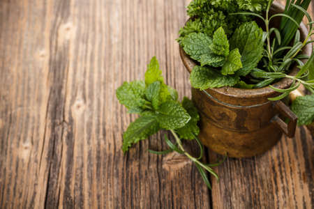 cooking utensils: Mortar with herbs on rustic wooden background