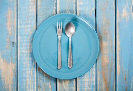 Modré prázdné talíře s vidličkou a lžící