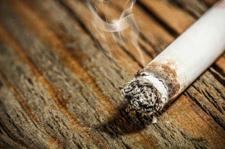 cigarette smoke: Cigarette on rustic wooden background Stock Photo