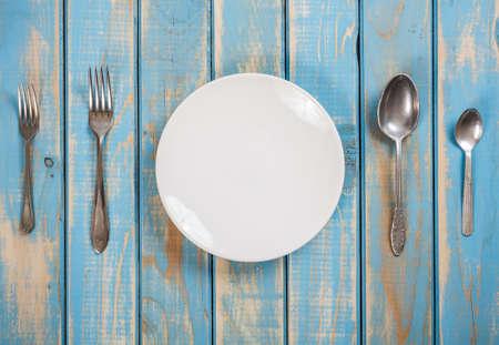 Foto van een diner instellen op een blauwe houten plank Stockfoto