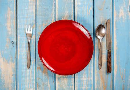 Пустые красный пластина на синем деревянный стол с ножом, ложкой и вилкой