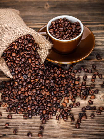 Roasted coffee beans in hessian sack and cup on wooden background  photo