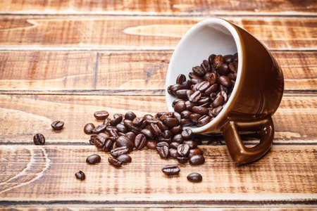 overturned: Overturned coffee cup with beans Stock Photo