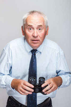 Shocked man searching with binoculars and looking surprised photo