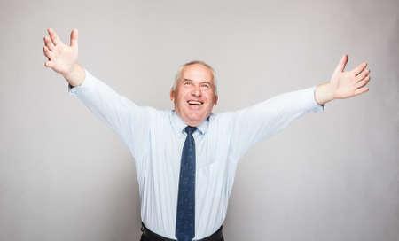 fortunate: Happy senior businessman on gray background