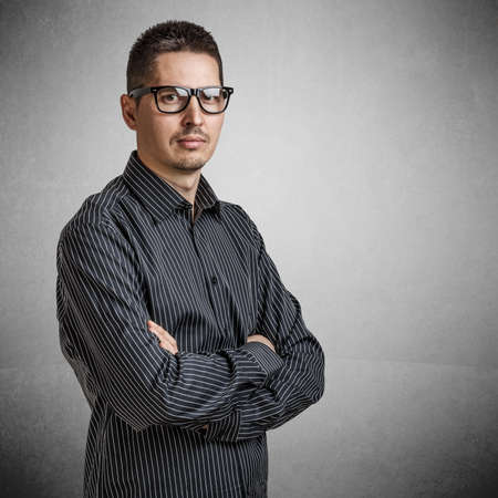 Casual young businessman standing arms crossed photo