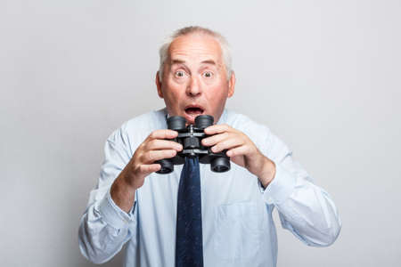 Shocked businessman searching with binoculars and looking surprised photo
