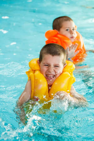 Boys in life jacket learning to swim in the swimming pool  photo