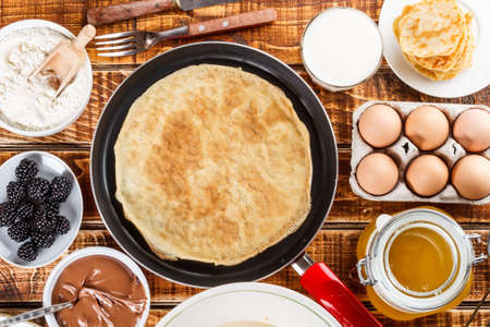 griddle: Frying pan with pancake and pancake ingredients Stock Photo