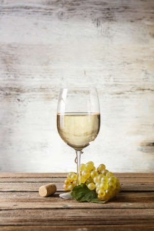 white wine glass: Wineglass with white wine on wooden table