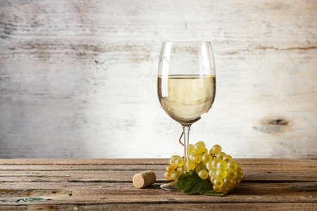 ビンテージ木製テーブルの上の白ワインのガラス 写真素材