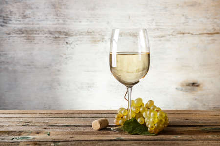 Glass of white wine on vintage wooden table Imagens