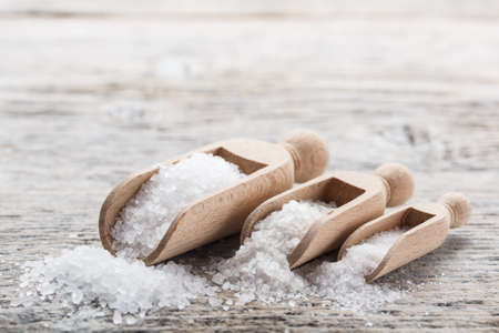 Sea salt poured from wooden scoop