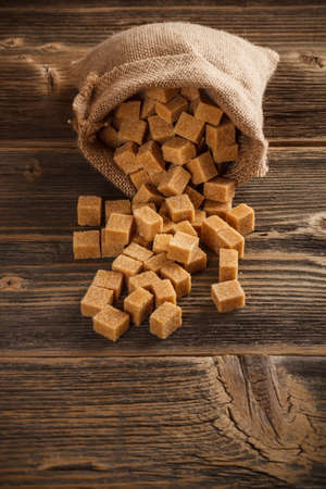 Brown sugar cubes in sack on wooden background photo