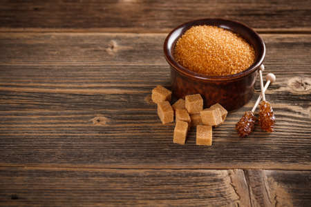 Brown sugar on old wooden background, space for text photo