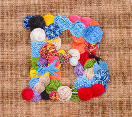 b ball: Letter B made of knitting yarn on burlap background