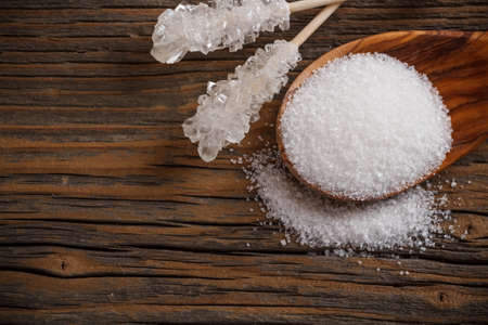 White sugar on wooden spoon