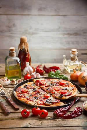 slice of pizza: Pizza made with salami, mozzarella, mushrooms, olives and tomato sauce  Stock Photo