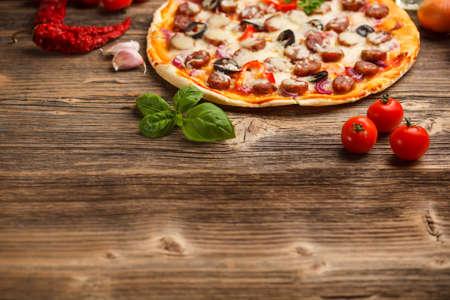 美味的意大利比薩餅送達質樸的木桌上 版權商用圖片