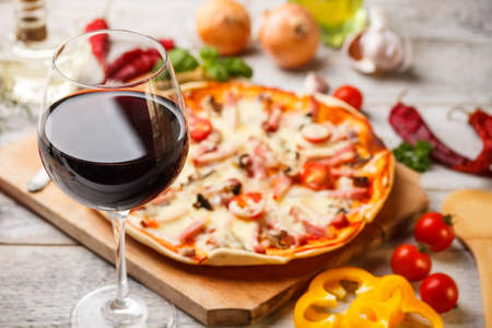 Glass of red wine with pizza on cutting board photo