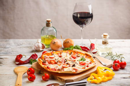 Fresh homemade pizza served with red wine photo