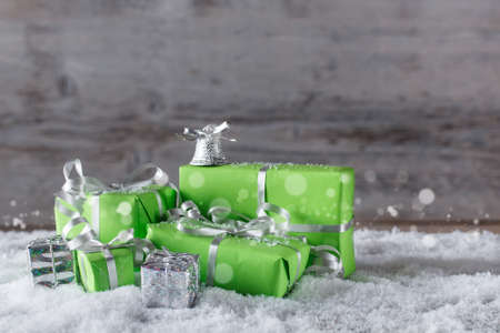 Stack of green and silver Christmas presents in snow  photo