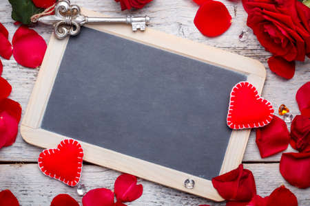 Blank black chalkboard with petals and handmade hearts Stock Photo - 25212878