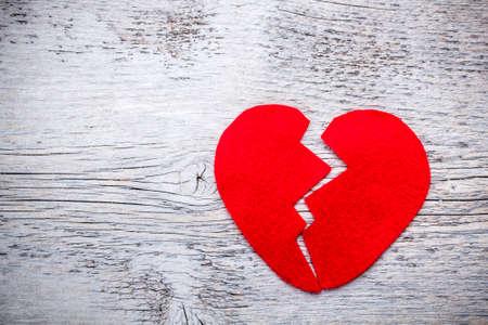 corazon roto: Rojo corazón roto en el fondo de madera desgastada
