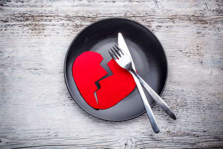 heartsickness: Plate with broken heart on wooden background Stock Photo