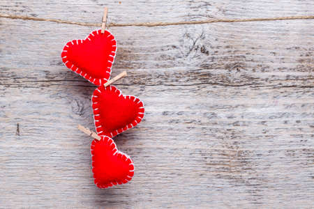 Three love hearts hanging on wooden texture background photo