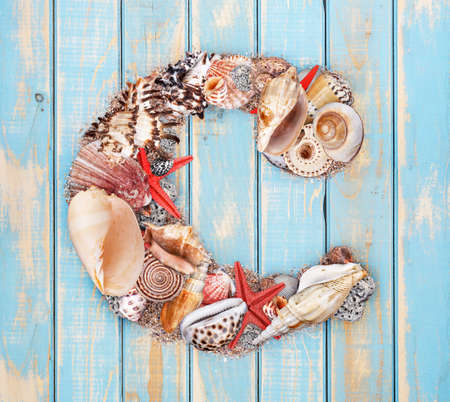 Letter C made of seashell on blue wooden background photo