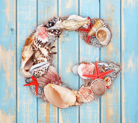 Letter G made of seashell on blue wooden background photo