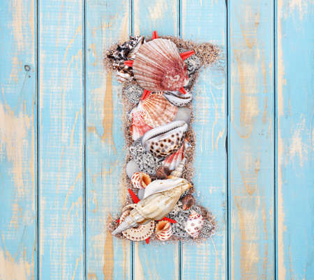 Letter I made of seashell on blue wooden background photo