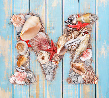 Letter M made of seashell on blue wooden background photo