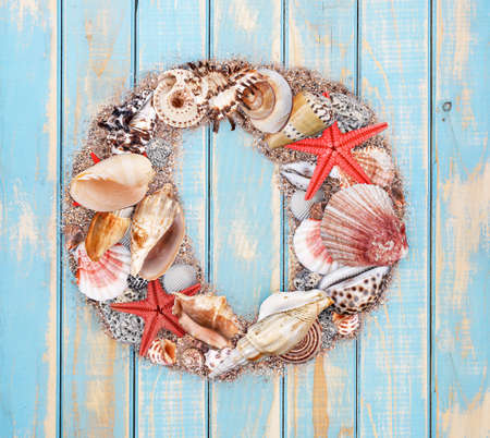 Letter O made of seashell on blue wooden background photo