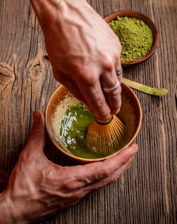 tea hot drink: Beating matcha powder and water with bamboo whisk Stock Photo