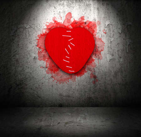 Stitched felt broken heart on old grunge obsolete wall with spotlight photo