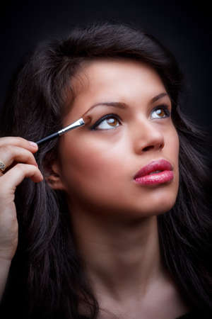Eye makeup woman applying eyeshadow powder  photo