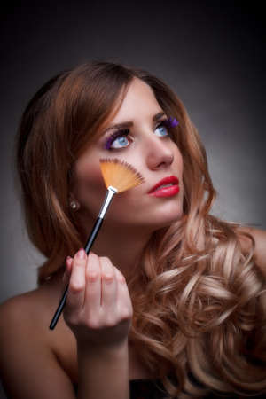 Beauty portrait of young woman with the makeup brush over grey background  photo