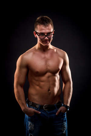 Young muscular man undressed to the waist has his hands in his pockets photo
