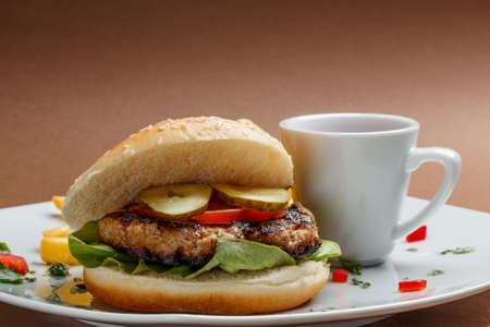 Hamburger in white plate on brown background photo