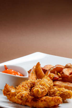 Crispy chicken breast strips with sauce photo